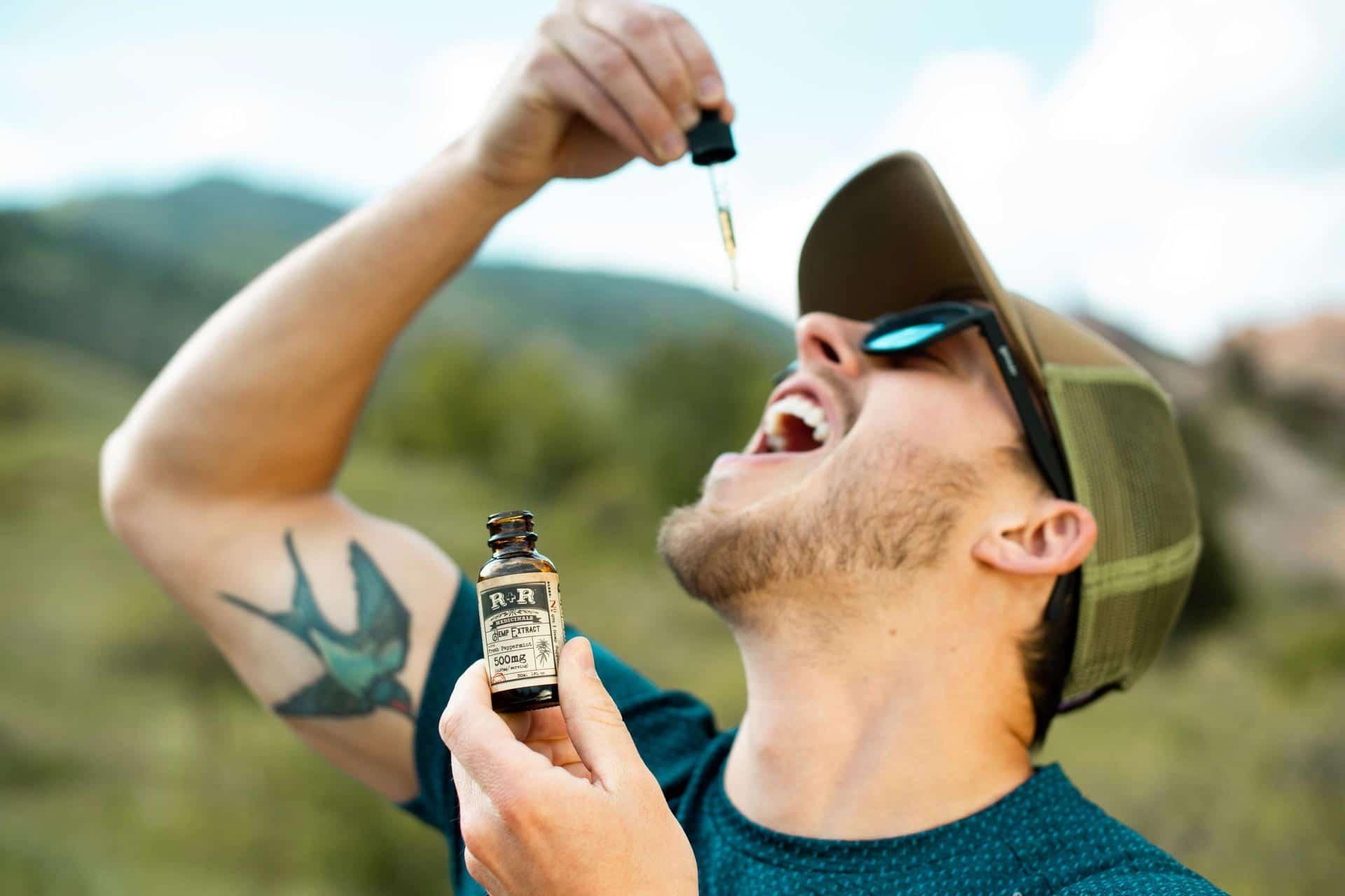 homme qui se met de l'huile cbd sous la langue